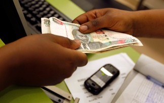 A customer conducts a mobile money transfer, known as M-Pesa, inside the Safaricom mobile phone care centre in the central business district of Kenya's capital Nairobi July 15, 2013. Picture taken July 15. REUTERS/Thomas Mukoya (KENYA - Tags: BUSINESS TELECOMS) - RTX13QOM